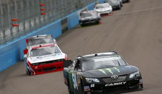 Kyle Busch leads a group of drivers through the first turn during a NASCAR Nationwide auto race Saturday, March 1, 2014, in Avondale, Ariz. (AP Photo/Ross D. Franklin)