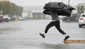 Manufacturing Assembly worker Terry Young, 24, of Rialto, Calif., uses a sheet of plastic to protect himself from a downpour Friday, Feb. 28, 2014, as he jumps a flooded parking lot from a wood pallet to get to a food truck during his break in Anaheim, Calif. The first wave of a powerful Pacific storm spread rain and snow early Friday through much of California, where communities endangered by a wildfire just weeks ago now faced the threat of mud and debris flows. (AP Photo/The Orange County Register, Ken Steinhardt) MAGS OUT; LOS ANGELES TIMES OUT