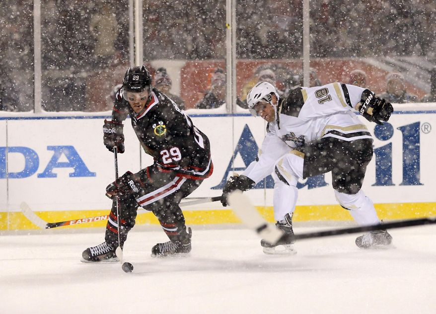 Chicago Blackhawks left wing Bryan Bickell (29) handles the puck away from Pittsburgh Penguins left wing James Neal (18) during the first period of an NHL Stadium Series hockey game at Soldier Field on Saturday, March 1, 2014, in Chicago. (AP Photo/Charles Rex Arbogast)
