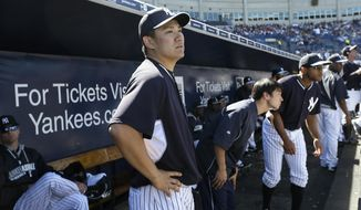New York Yankees pitcher Masahiro Tanaka stands in the dugout before pitching in an exhibition baseball game against the Philadelphia Phillies Saturday, March 1, 2014, in Tampa, Fla. (AP Photo/Charlie Neibergall)