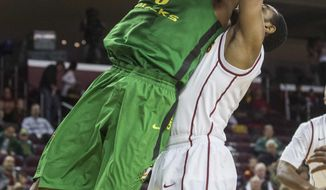 Oregon forward Mike Moser, left, goes up against Southern California forward Roschon Prince during the first half of an NCAA college basketball game Saturday, March 1, 2014, in Los Angeles. (AP Photo/Ringo H.W. Chiu)