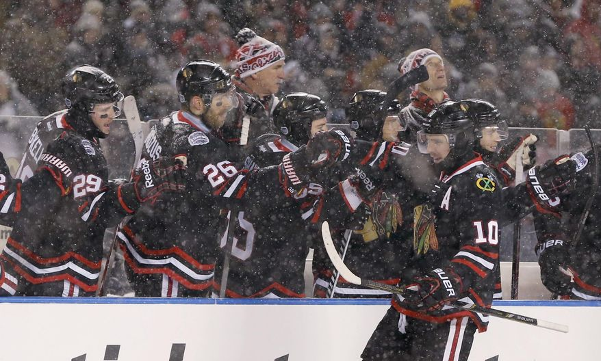 Chicago Blackhawks left wing Patrick Sharp (10) celebrates his goal with teammates on the bench during the first period of an NHL Stadium Series hockey game against the Pittsburgh Penguins at Soldier Field on Saturday, March 1, 2014, in Chicago. (AP Photo/Charles Rex Arbogast)