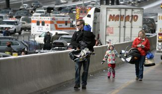 A family involved a massive pileup accident on Interstate 25, who declined to give their names, walk up the on ramp that leads from South Washington Street onto Interstate 25, in Denver, Saturday, March 1, 2014.  Authorities say one person was killed and 30 others were injured in the giant pileup. (AP Photo/The Denver Post, Kathryn Scott Osler) MAGS OUT; TV OUT; INTERNET OUT; NO SALES; NEW YORK POST OUT; NEW YORK DAILY NEWS OUT