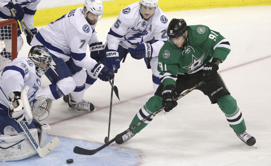 Dallas Stars center Tyler Seguin (91) tries to shoot the puck against Tampa Bay Lightning goalie Cedrick Desjardins (31) with defensemen Radko Gudas (7) and Matt Carle (25) looking on during the first period of an NHL hockey game Saturday, March 1, 2014, in Dallas. (AP Photo/LM Otero)