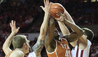 Oklahoma forward Tyler Neal, right, and forward Ryan Spangler defend as Texas center Prince Ibeh (44) goes to the basket during the second half of an NCAA college basketball game in Norman, Okla., Saturday, March 1, 2014. Oklahoma won 77-65. (AP Photo/Alonzo Adams)