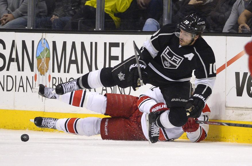 Los Angeles Kings center Mike Richards, top, and Carolina Hurricanes center Eric Staal vie for the puck during the second period of an NHL hockey game, Saturday, March 1, 2014, in Los Angeles. (AP Photo/Mark J. Terrill)