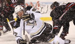 Pittsburgh Penguins center Sidney Crosby (87) falls to the ice after being checked by Chicago Blackhawks center Jonathan Toews, right, during the first period of an NHL Stadium Series hockey game at Soldier Field on Saturday, March 1, 2014, in Chicago. (AP Photo/Charles Rex Arbogast)