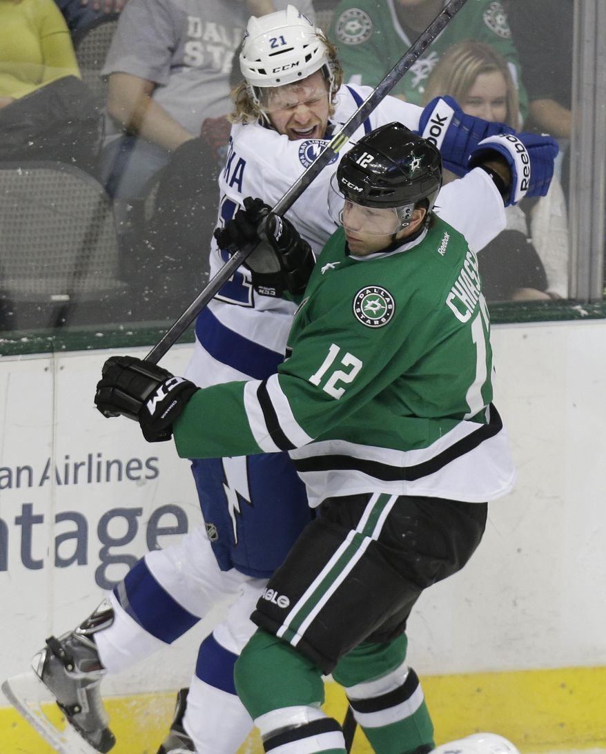 Tampa Bay Lightning defenseman Mike Kostka (21) is hit hard by Dallas Stars right wing Alex Chiasson (12) during the first period of an NHL hockey game Saturday, March 1, 2014, in Dallas. (AP Photo/LM Otero)