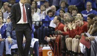 Louisville coach Rick Pitino, left, walks past the Louisville bench in the second half of an NCAA college basketball game against Memphis in Memphis, Tenn., Saturday, March 1, 2014. Memphis defeated Louisville 72-66. (AP Photo/Danny Johnston)