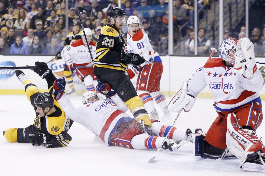 CORRECTS THAT BRUINS SHAWN THORNTON, NOT SHOWN, SCORED THE GOAL, NOT GREGORY CAMPBELL AS ORIGINALLY SENT  - Boston Bruins' Gregory Campbell (11) falls after scoring on Washington Capitals' Braden Holtby, right, in the second period of an NHL hockey game in Boston, Saturday, March 1, 2014. (AP Photo/Michael Dwyer)