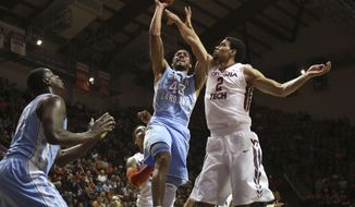 North Carolina's James Michael McAdoo (43)  scores past the defense of Joey van Zegeren (2) right, of Virginia Tech during the first half of an NCAA college basketball game in Blacksburg, Va., Saturday, March 1, 2014. (AP Photo/The Roanoke Times, Matt Gentry) LOCAL TV OUT; LOCAL INTERNET OUT; LOCAL PRINT OUT (SALEM TIMES REGISTER; FINCASTLE HERALD; CHRISTIANSBURG NEWS MESSENGER; RADFORD NEWS JOURNAL; ROANOKE STAR SENTINEL