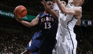Illinois' Tracy Abrams (13) dishes off against Michigan State's Gavin Schilling, right, and Adreian Payne during the first half of an NCAA college basketball game, Saturday, March 1, 2014, in East Lansing, Mich. (AP Photo/Al Goldis)