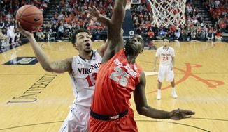 Virginia forward Anthony Gill (13) takes a shot over Syracuse forward Rakeem Christmas (25) during an NCAA College basketball game in Charlottesville, Va., Saturday, March 1, 2014. Virginia won the game 75-56. (AP Photo/Steve Helber)
