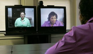 FILE - In this Tuesday, Dec. 7, 2004 photo, prison inmate Vanessa Buffington, left, talks in Marysville, Ohio with her former sister-in-law, Barbara Palmore, right, in Cleveland via a video link from the office of The Eastside Consortium Prison Visitation Program/Project IMPACT. Jail officials in two other Ohio counties, Montgomery and Warren, are planning to allow inmates to meet with their lawyers, family and friends using remote video access. (AP Photo/The Plain Dealer, David I. Andersen)