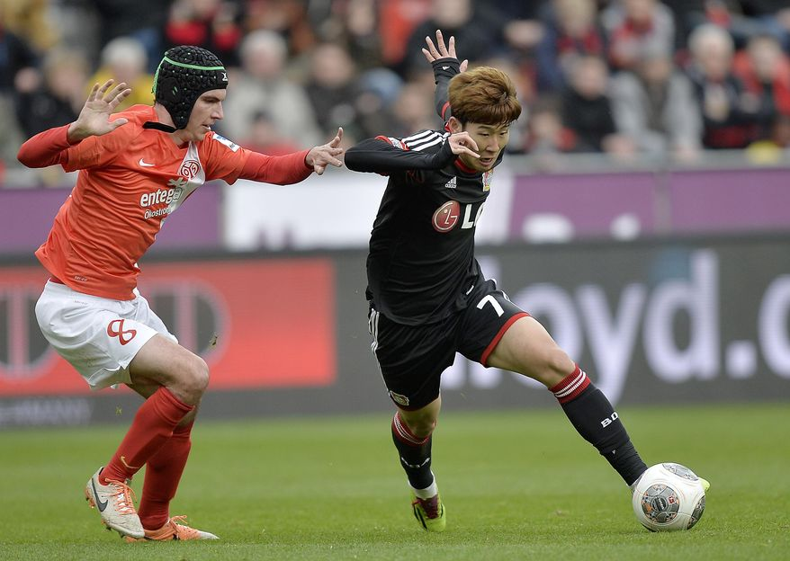 Mainz's Christoph Moritz, left, and Leverkusen's Son Heung-min  of South Korea challenge for the ball during the German Bundesliga soccer match between Bayer Leverkusen and FSV Mainz 05 in Leverkusen,  Germany, Saturday, March 1, 2014. (AP Photo/Martin Meissner)