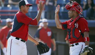 Washington Nationals relief pitcher Luis Ayala, left, celebrates with catcher Sandy Leon after a spring training baseball game against the Atlanta Braves, Saturday, March 1, 2014, in Viera, Fla. The Nationals won 16-15. (AP Photo/Alex Brandon)