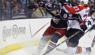 Columbus Blue Jackets' David Savard, left, and Florida Panthers' Nick Bjugstad chase a loose puck during the first period of an NHL hockey game Saturday, March 1, 2014, in Columbus, Ohio. (AP Photo/Jay LaPrete)