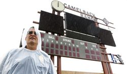 Phoenix Police Department patrolman Kevin Sanchez stands in the rain at Camelback Ranch where the Chicago White Sox-Cleveland Indians exhibition baseball game was postponed due to rain in Glendale, Ariz., Saturday, March 1, 2014. (AP Photo/Paul Sancya)