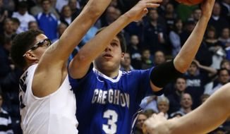 Creighton's Doug McDermott shoots past Xavier's Isaiah Philmore during the first half of an NCAA college basketball game in Cincinnati on Saturday, March 1, 2014. (AP Photo/Tom Uhlman)