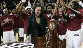 South Carolina coach Dawn Staley looks at the trophy after the team won the Southeastern Conference title with a 67-56 win over Georgia in an NCAA college basketball game Thursday, Feb. 27, 2014, in Columbia, S.C. (AP Photo/Mary Ann Chastain)