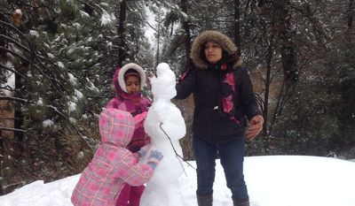 Shobha Sharma, 39, of San Diego, right, helps her daughters, Aditi, 8, and Amoli, 3, build a snow figure near Running Springs, Calif. (AP Photo/The Press-Enterprise, Mark Muckenfuss) MANDATORY CREDIT: THE PRESS-ENTERPRISE, MARK MUCKENFUSS