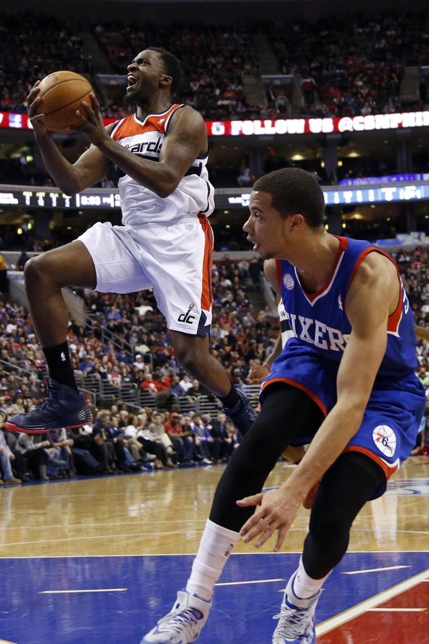 Washington Wizards' Martell Webster, left, goes up for a shot as Philadelphia 76ers' Michael Carter-Williams looks on during the first half of an NBA basketball game, Saturday, March 1, 2014, in Philadelphia. (AP Photo/Matt Slocum)