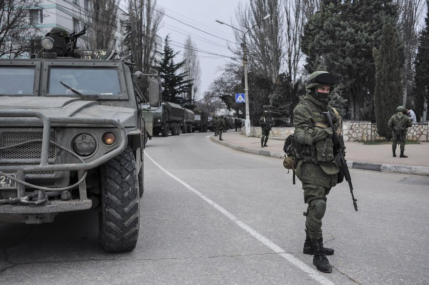 Troops in unmarked uniforms stand guard in Balaklava on the outskirts of Sevastopol, Ukraine, Saturday, March 1, 2014. An emblem on one of the vehicles and their number plates identify them as belonging to the Russian military. Ukrainian officials have accused Russia of sending new troops into Crimea, a strategic Russia-speaking region that hosts a major Russian navy base. The Kremlin hasn't responded to the accusations, but Russian lawmakers urged President Putin to act to protect Russians in Crimea. (AP Photo/Andrew Lubimov)