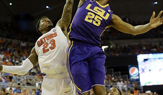 LSU forward Jordan Mickey (25) scores two points with Florida's Chris Walker (23) unable to block during the first half of an NCAA college basketball game on Saturday, March 1, 2014, in Gainesville, Fla. Floridfa defeated LSU 79-61.(AP Photo/Phil Sandlin)