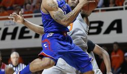 Kansas guard Frank Mason (0) goes up for a shot in front of Oklahoma State guard Marcus Smart (33) during the first half of an NCAA college basketball game in Stillwater, Okla., Saturday, March 1, 2014. (AP Photo/Sue Ogrocki)