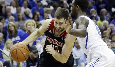 Louisville's Luke Hancock (11) dribbles the ball around Memphis' Damien Wilson in the first half of an NCAA college basketball game in Memphis, Tenn., Saturday, March 1, 2014. (AP Photo/Danny Johnston)