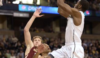 Wake Forest guard Codi Miller-McIntyre (0) shoots over Boston College guard Olivier Hanlan (21) during the first half of an NCAA college basketball game in Winston-Salem, N.C., Saturday, March 1, 2014. (AP Photo/The Journal, Bruce Chapman)