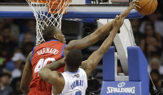Philadelphia 76ers' Jarvis Varnado, left, blocks a shot attempt by Orlando Magic's Adonis Thomas (8) during the first half of an NBA basketball game in Orlando, Fla., Sunday, March 2, 2014. (AP Photo/John Raoux)