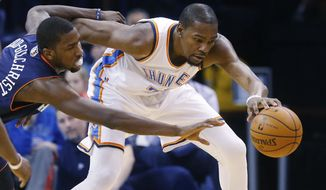 Oklahoma City Thunder forward Kevin Durant (35) keeps the ball away from Charlotte Bobcats forward Michael Kidd-Gilchrist (14) during the first quarter of an NBA basketball game in Oklahoma City, Sunday, March 2, 2014. (AP Photo/Sue Ogrocki)