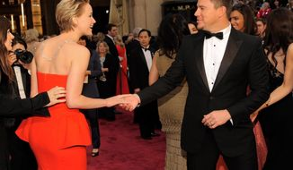 Jennifer Lawrence, left, and Channing Tatum shake hands at the Oscars on Sunday, March 2, 2014, at the Dolby Theatre in Los Angeles.  (Photo by Chris Pizzello/Invision/AP)
