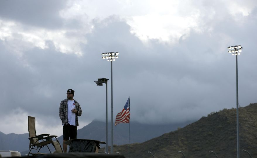 A spectator looks around as storm clouds move in for a rain-shortened NASCAR Nationwide auto race on Saturday, March 1, 2014, in Avondale, Ariz. Kyle Busch was declared the winner. (AP Photo/Ross D. Franklin)