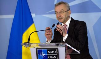 Ukraine's Ambassador to NATO Ihor Dolhov adjusts the microphones prior to speaking during a media conference at NATO headquarters in Brussels on Sunday, March 2, 2014. NATO is called emergency talks on Sunday regarding the escalating crisis in Ukraine. (AP Photo/Virginia Mayo)