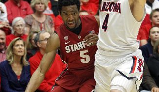 Stanford's Chasson Randle (5) works around Arizona's T.J. McConnell (4) during the first half of an NCAA college basketball game Sunday, March 2, 2014, in Tucson, Ariz. (AP Photo/John MIller)