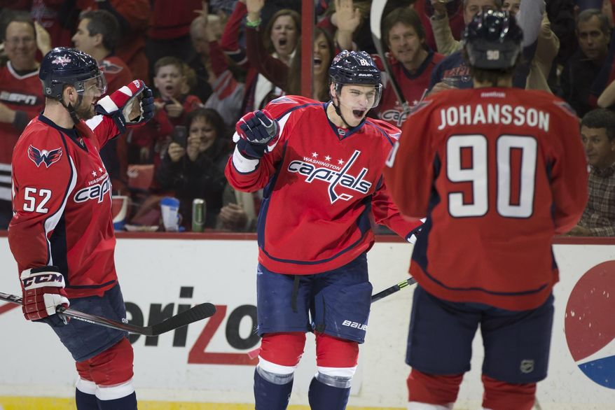 Washington Capitals defenseman Dmitry Orlov, center, celebrates his first-period goal against the Philadelphia Flyers with teammates defenseman Mike Green, left, and center Marcus Johansson, Sunday, March 2, 2014, in Washington. (AP Photo/ Evan Vucci)