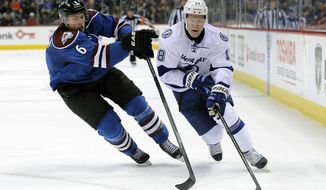 Colorado Avalanche defenseman Erik Johnson, left, and Tampa Bay Lightning left wing Ondrej Palat, right, of the Czech Republic, fight for the puck in the second period of an NHL hockey game, Sunday, March 2, 2014 in Denver.  (AP Photo/Chris Schneider)