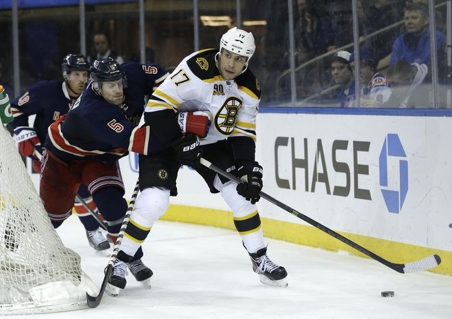 New York Rangers' Dan Girardi, left, tries to get to Boston Bruins' Milan Lucic during the third period of an NHL hockey game Sunday, March 2, 2014, in New York. The Bruins beat the Rangers 6-3. (AP Photo/Seth Wenig)