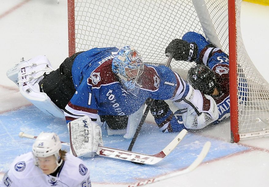 Colorado Avalanche center Maxime Talbot, right, slides into the goal past Avalanche goalie Semyon Varlamov, left, of Russia, in the first period of an NHL hockey game against the Tampa Bay Lightning, Sunday, March 2, 2014 in Denver. (AP Photo/Chris Schneider)