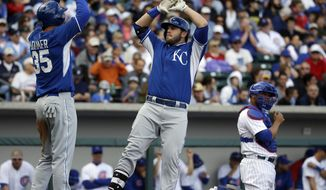 Kansas City Royals' Mike Moustakas, center, is congratulated by teammate Eric Hosmer (35) after hitting a two-run home run during the fourth inning of a spring exhibition baseball game against the Chicago Cubs, Sunday, March 2, 2014, in Mesa, Ariz. (AP Photo/Morry Gash)