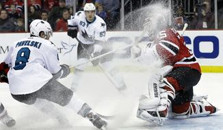 San Jose Sharks' Joe Pavelski (8) throws up ice as he shoots against New Jersey Devils goalie Cory Schneider (35) during the first period of an NHL hockey game on Sunday, March. 2, 2014, in Newark, N.J. (AP Photo/Mel Evans)