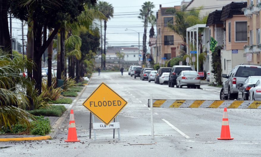 ** FILE ** A barricade still stands up along Ocean Boulevard between 66th and 72nd Place, along the Peninsula in Long Beach, Calif., Sunday, March 2, 2014. Flooding occurred when heavy surf eroded the protective sand berm Saturday night, resulting in 20 homes on Ocean Blvd between 66th and 72nd Place, sustaining damage to either living levels or parking areas. (AP Photo/Daily Breeze, Stephen Carr)