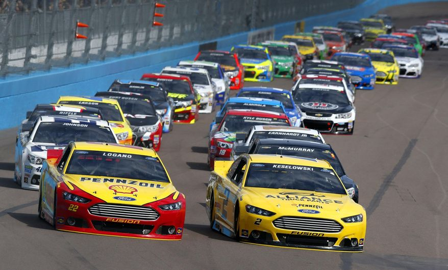 Joey Logano (22) and Brad Keselowski (2) lead into the first turn at the start of the NASCAR Sprint Cup Series auto race Sunday, March 2, 2014, in Avondale, Ariz. (AP Photo/Ross D. Franklin)