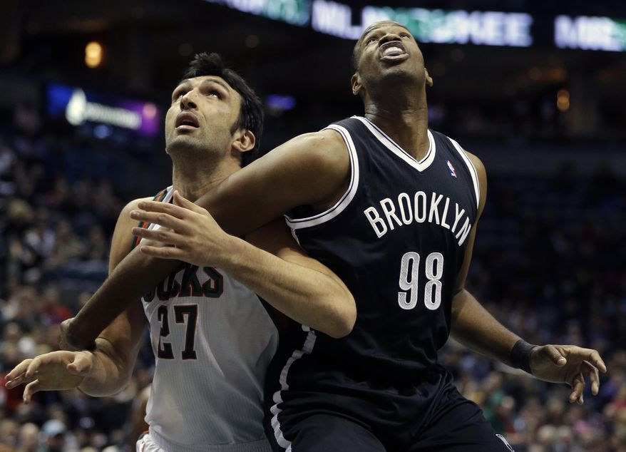 Brooklyn Nets' Jason Collins (98) and Milwaukee Bucks' ZaZa Pachulia, left, look for a rebound in the first half of an NBA basketball game, Saturday, March 1, 2014, in Milwaukee. (AP Photo/Jeffrey Phelps)