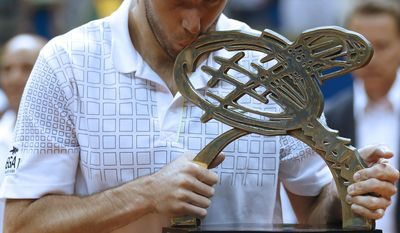 Argentina's Federico Delbonis kisses the Brazil Open ATP tennis trophy as he poses for pictures after defeating Italy's Paolo Lorenzi in Sao Paulo, Brazil, Sunday, March 2, 2014. (AP Photo/Andre Penner)