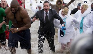 """""""The Tonight Show"""" host Jimmy Fallon, center, exits the water during the Chicago Polar Plunge, Sunday, March 2, 2014, in Chicago. Fallon joined Chicago Mayor Rahm Emanuel in the event. (AP Photo/Andrew A. Nelles)"""