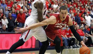 Stanford's Dwight Powell (33) tries to dribble around the defense of Arizona's Rondae Hollis-Jefferson during the first half of an NCAA college basketball game  Sunday, March 2, 2014, in Tucson, Ariz. (AP Photo/John MIller)