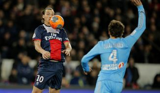 Paris Saint Germain's Zlatan Ibrahimovic of Sweden, left challenges for the ball with Marseille's Lucas Mendes of France during their French League One soccer match, at the Parc des Princes stadium, in Paris, Sunday, March 2 , 2014. (AP Photo/Lionel Cironneau)